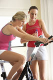 Jovem mulher na bicicleta de exercício com instrutor Fotografia de Stock