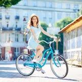 A jovem mulher na bicicleta do vintage olha a câmera, verão fotos de stock