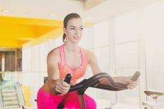 Jovem mulher na bicicleta dos artigos de papelaria do passeio do gym Fotos de Stock Royalty Free