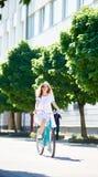 A jovem mulher na bicicleta monta a pena sozinha a rua da cidade Imagem de Stock