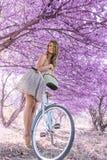 Jovem mulher na bicicleta na floresta do rosa da fantasia foto de stock royalty free