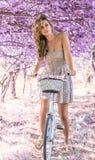 Jovem mulher na bicicleta na floresta do rosa da fantasia foto de stock