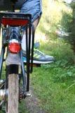 Jovem mulher na bicicleta que está na estrada e que olha a em algum lugar Foto de Stock Royalty Free