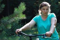 Jovem mulher na bicicleta que está na estrada e que olha a em algum lugar Foto de Stock
