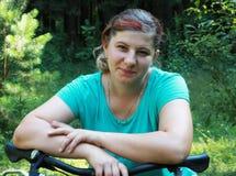 Jovem mulher na bicicleta que está na estrada e que olha a em algum lugar Imagens de Stock