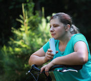 Jovem mulher na bicicleta que está na estrada e que olha a em algum lugar Fotos de Stock Royalty Free