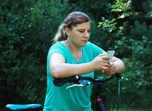 Jovem mulher na bicicleta que está na estrada e que olha a em algum lugar Imagem de Stock Royalty Free