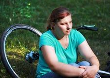 Jovem mulher na bicicleta que está na estrada e que olha a em algum lugar Fotografia de Stock