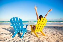 A jovem mulher na cadeira de praia levantou suas mãos acima fotografia de stock royalty free