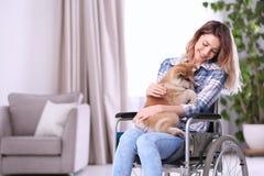 Jovem mulher na cadeira de rodas com cachorrinho imagem de stock royalty free