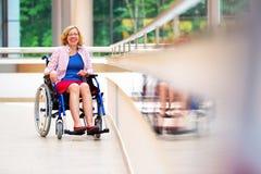 Jovem mulher na cadeira de rodas no centro médico Imagem de Stock