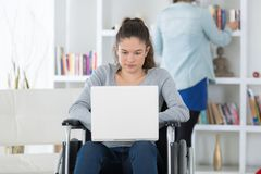 Jovem mulher na cadeira de rodas usando o portátil fotografia de stock royalty free