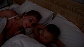 Jovem mulher na cama com seu filho novo Mamã e filho que acordam junto filme