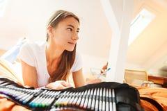 Jovem mulher na cama, tirando no livro para colorir Foto de Stock Royalty Free