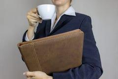 Jovem mulher na camisa branca e terno que guarda um dobrador da xícara de café e do couro em suas mãos Conceito do negócio imagem de stock royalty free