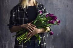 Jovem mulher na camisa de manta que guarda o ramalhete de tulipas roxas de terry Foto de Stock