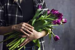 Jovem mulher na camisa de manta que guarda o ramalhete de tulipas roxas de terry Imagens de Stock