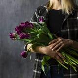 Jovem mulher na camisa de manta que guarda o ramalhete de tulipas roxas de terry Imagem de Stock