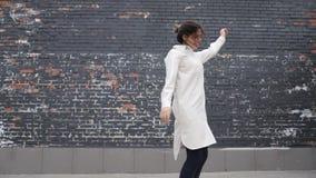 Jovem mulher na camisa longa e nas calças de brim que dançam na rua, parede de tijolo preta filme
