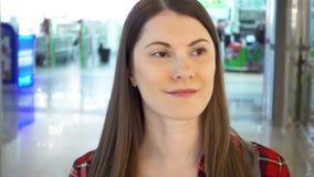 Jovem mulher na camisa vermelha que anda em torno do sorriso da alameda Cliente fêmea no corredor do shopping video estoque