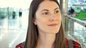 Jovem mulher na camisa vermelha que anda em torno do sorriso da alameda Cliente fêmea no corredor do shopping vídeos de arquivo