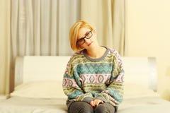 Jovem mulher na camiseta colorida que senta-se na cama Imagens de Stock