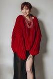 Jovem mulher na camiseta desproporcionado vermelha e na saia preta Fotografia de Stock