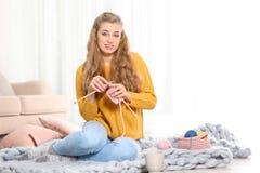Jovem mulher na camiseta morna acolhedor que faz malha com agulhas foto de stock