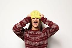 Jovem mulher na camiseta morna e no chapéu feito malha no fundo branco imagens de stock