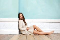 Jovem mulher na camiseta que senta-se no assoalho de madeira em casa Imagens de Stock Royalty Free