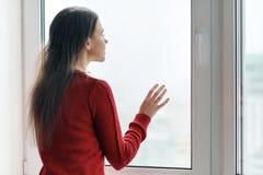 A jovem mulher na camiseta vermelha que olha para fora a janela, fêmea pôs suas mãos sobre o vidro de janela, vista lateral, jane fotografia de stock royalty free