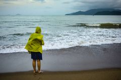 Jovem mulher na capa de chuva amarela perto do oceano na tempestade foto de stock royalty free
