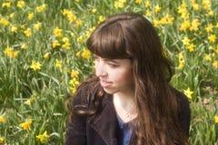 Jovem mulher na cena da mola com narcisos amarelos imagem de stock