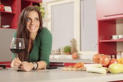 Jovem mulher na cozinha com vidro do vinho tinto Imagens de Stock Royalty Free