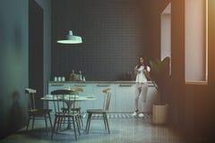 Jovem mulher na cozinha e na sala de jantar cinzentas do tijolo foto de stock royalty free