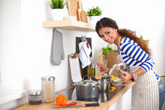 Jovem mulher na cozinha que prepara um alimento Fotografia de Stock