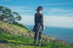 Jovem mulher na cume pelo mar fotos de stock
