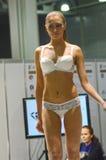 Jovem mulher na expo branca Moscou de Lingrie do desfile de moda do olhar do lingrie Foto de Stock