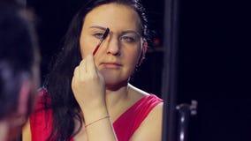 A jovem mulher na frente do espelho dá forma a suas sobrancelhas vídeos de arquivo