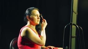 A jovem mulher na frente do espelho dá forma a suas sobrancelhas com uma escova video estoque