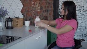 Jovem mulher na garrafa da abertura da cadeira de rodas com leite na cozinha vídeos de arquivo