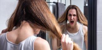 Jovem mulher na gritaria da crise na frente de seu espelho Imagem de Stock Royalty Free