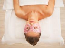 Jovem mulher na máscara de olho que coloca na tabela da massagem foto de stock