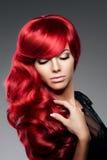 A jovem mulher na moda da forma luxuosa com vermelho ondulou o cabelo Menina w Fotos de Stock