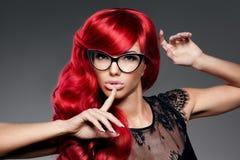 A jovem mulher na moda da forma luxuosa com vermelho ondulou o cabelo nos glas Imagem de Stock