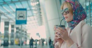 A jovem mulher na moda no revestimento, em óculos de sol e no lenço bege em seu cabelo louro está bebendo o café através do tubul vídeos de arquivo