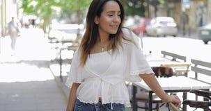 Jovem mulher na moda que está em uma rua urbana filme