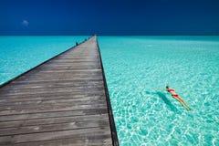 A jovem mulher na natação vermelha do biquini ao lado do molhe nos azuis celestes molha fotos de stock royalty free