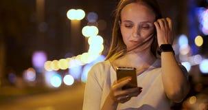 A jovem mulher na noite na cidade chama um t?xi atrav?s do smartphone vídeos de arquivo