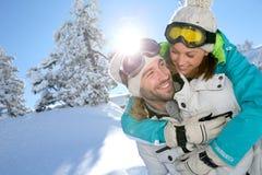 Jovem mulher na parte de trás de seu noivo nas montanhas nevado Imagens de Stock Royalty Free